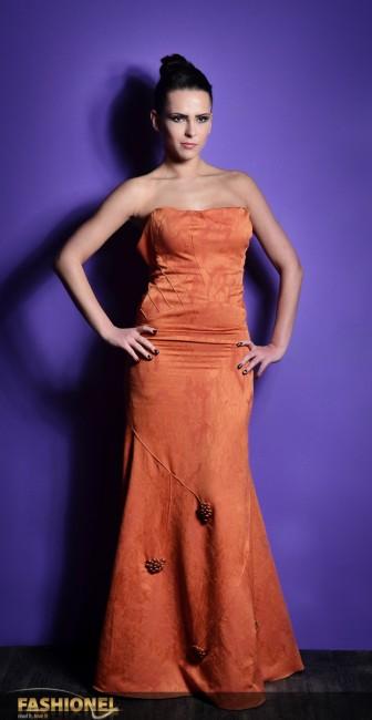 Секирарски: . Фустанот во портокалова боја е изработен од жакард од свила и волна со рачна изработка. Овој модел е дел од колекцијата со која се претставив на Париската Модна Недела која беше инспирирана од модата на раниот 20ти век