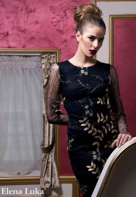 Црн коктел фустан, изработен од чипка со златни детали распоредени по површината.